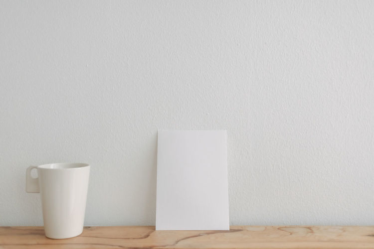 Close-up of coffee cup on table against wall at home