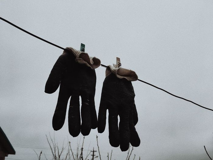 Low angle view of men hanging on rope against clear sky