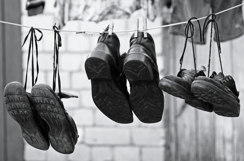 Close-up of footwear hanging on clothesline