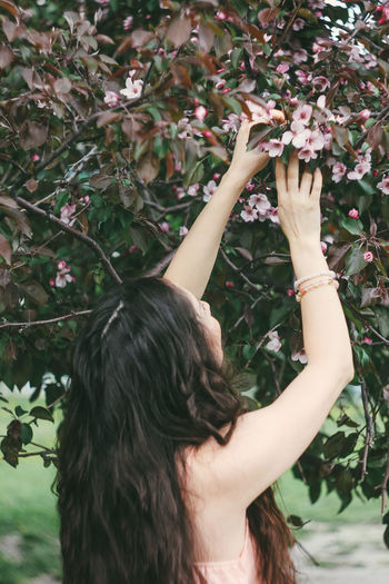 Midsection of woman with flowers in park