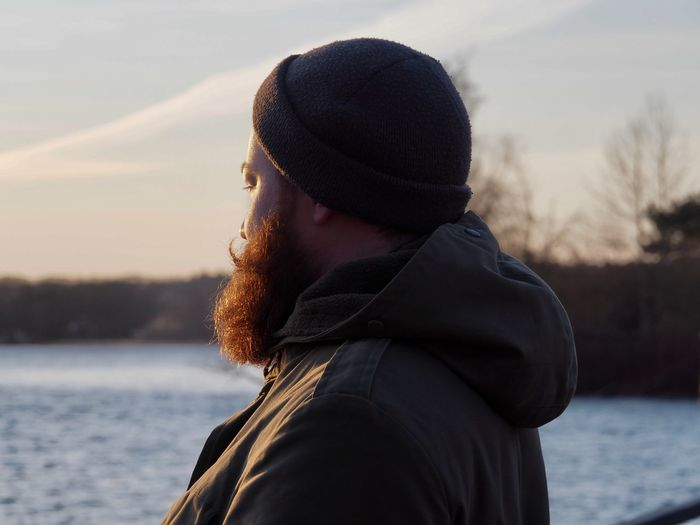 Beard Clothing Contemplation Day Focus On Foreground Hat Headshot Hipster Knit Hat Lake Leisure Activity Lifestyles Mustache Nature One Person Outdoors Portrait Real People Red Beard Side View Warm Clothing Water Winter Young Adult