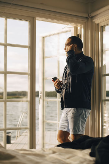 Man using phone while standing on window