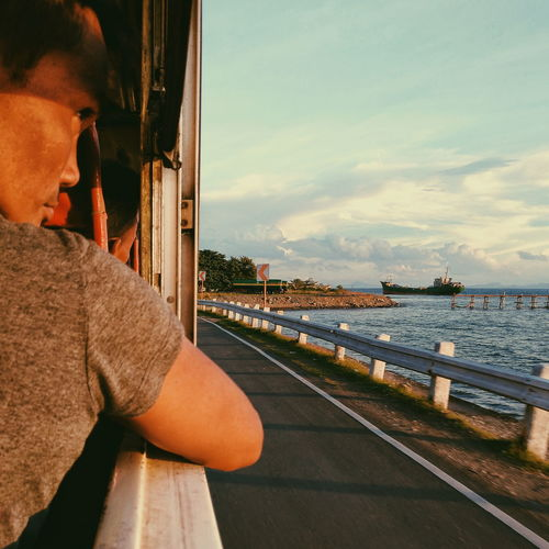 Side view of man looking at sea against sky