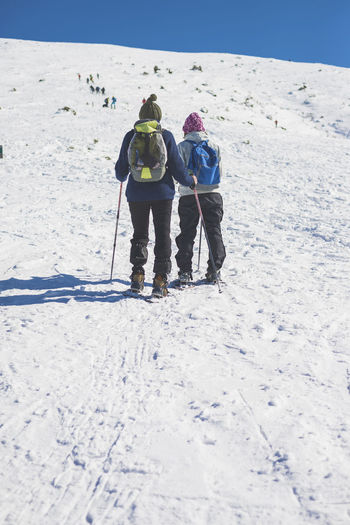 Two unrecognizable people walking through snow on the mountain Winter Snow Cold Temperature Mountain Rear View Leisure Activity Full Length Sport Clothing Holiday Warm Clothing Vacations Adventure Nature Trip Day Group Of People Ski Pole Winter Sport Mountain Range Outdoors Unrecognizable Person