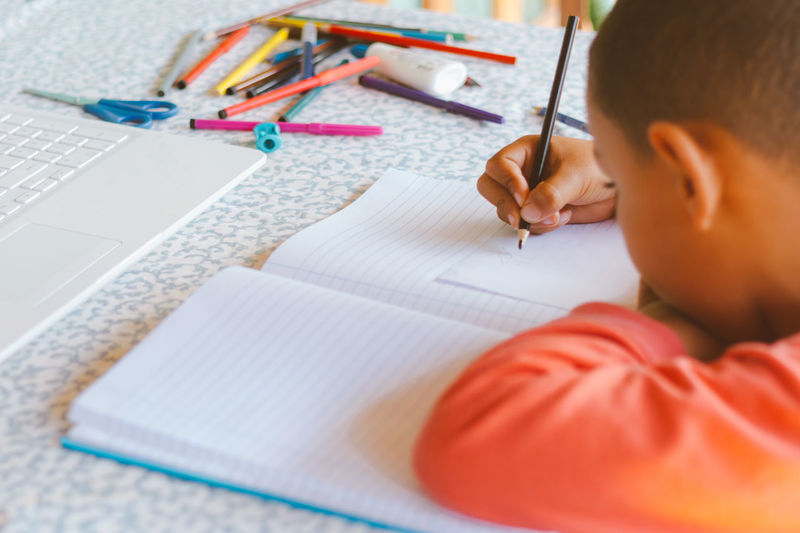 Midsection of boy reading book on table
