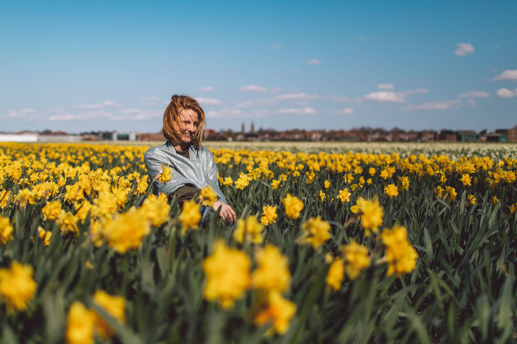 Girl sitting in a  yellow narcissus flowers field