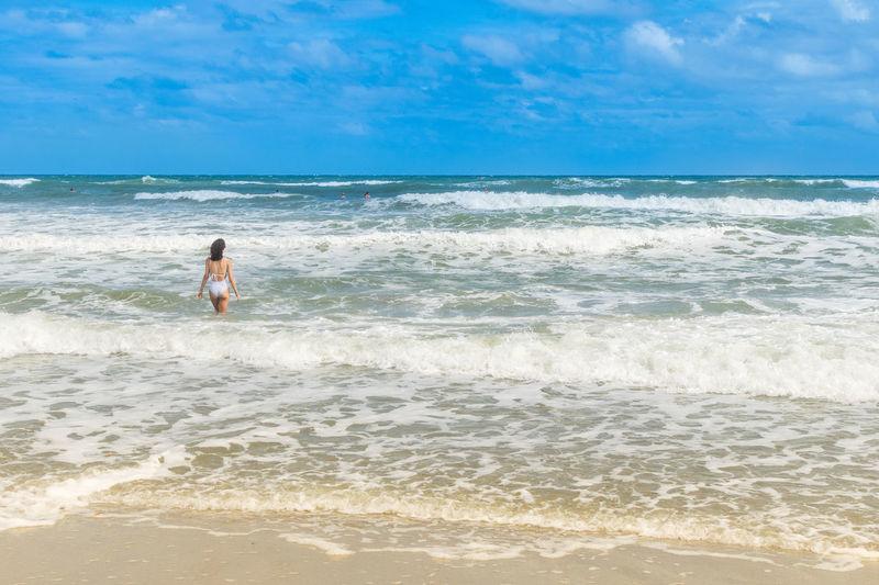 Rear view of woman in bikini at beach against sky