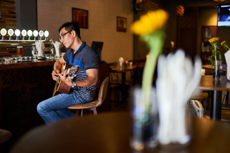 Side view of man playing guitar while sitting on chair