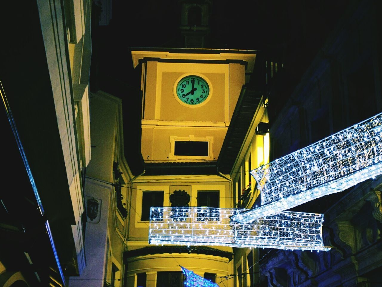 Low Angle View Of Christmas Lights Against Clock Tower At Night