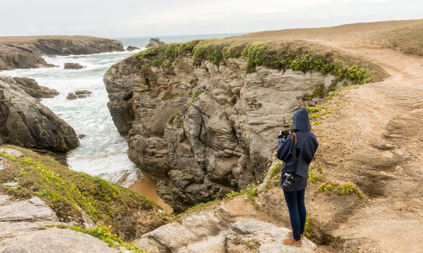 Full length rear view of woman standing on cliff by sea