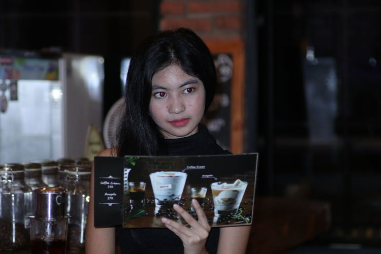 Portrait of woman holding drink at restaurant