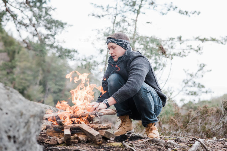 Low angle view of woman with bonfire on snow covered land