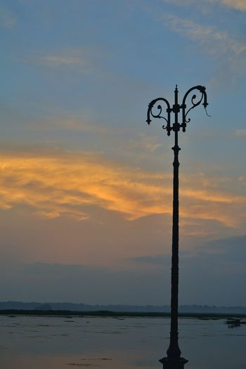 Silhouette wooden post by sea against sky during sunset