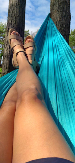 Low section of woman lying on hammock