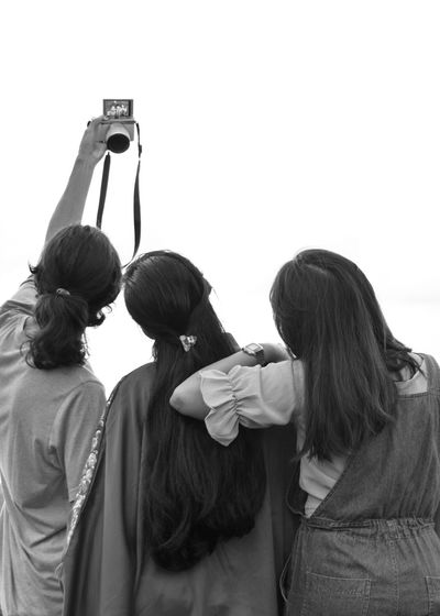 Rear View Of Female Friends Taking Selfie
