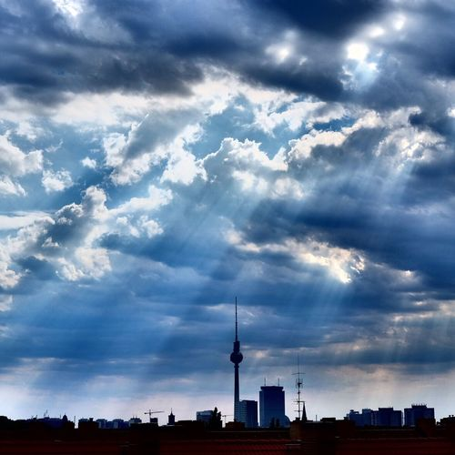 Communications tower in city against cloudy sky