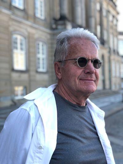 Senior man wearing sunglasses against building