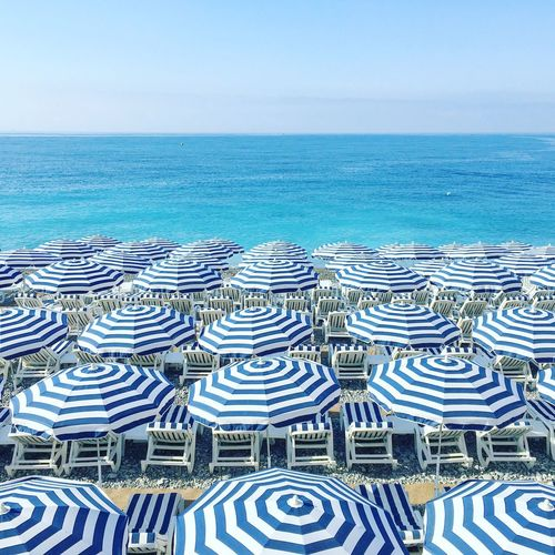 Blue Striped Parasols And Deck Chairs At Beach Against Sky
