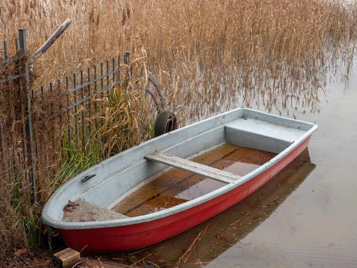 Abandoned Rowboat Water Nature Nautical Vessel Grass Day Plant No People Wood - Material Lake Tranquility Transportation Rowboat Absence Mode Of Transportation Outdoors Moored Reflection Land Reed - Grass Family