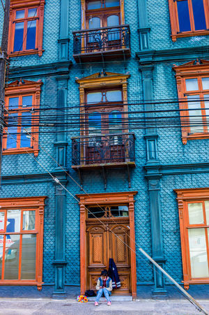 Waiting Architecture Blue And Orange Colors Building Exterior Built Structure City Day Façade Full Frame One Person Outdoors Sky Window