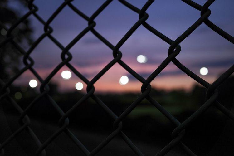 Full frame shot of chainlink fence against sky at sunset