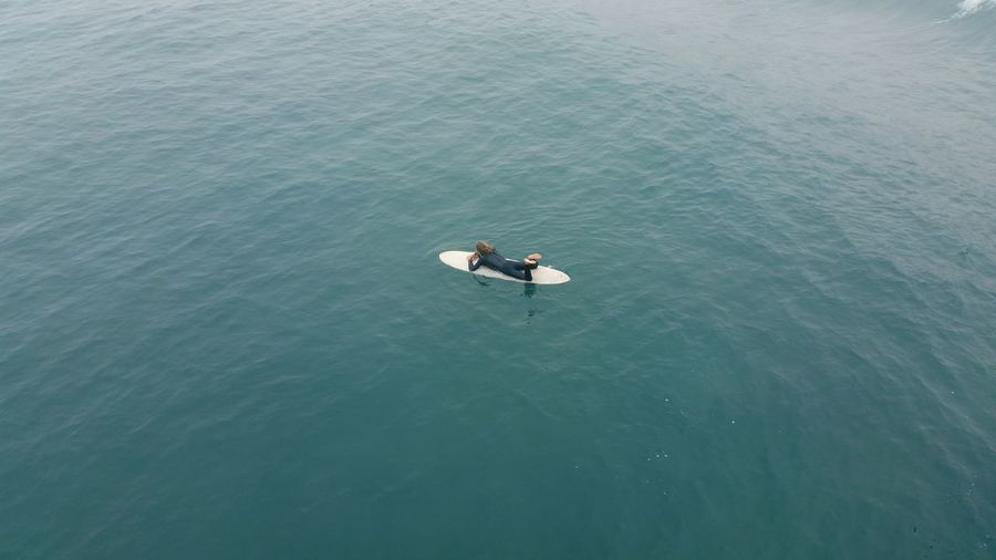 High angle view of surfer floating on water