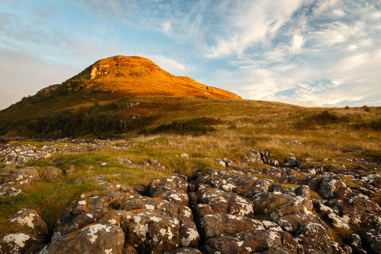 Scenic view of mountain peak in the golden glow of the setting sun. - Isle of Skye, 2017 Sky Rock Scenics - Nature Solid Cloud - Sky Rock - Object Beauty In Nature Mountain Environment Nature Landscape Tranquil Scene No People Non-urban Scene Day Land Tranquility Outdoors Grass Remote Mountain Peak Golden Hour Isle Of Skye Scotland Loch Snizort Beag EyeEm Best Shots EyeEm Nature Lover
