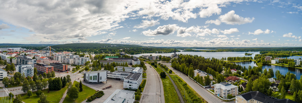 Wide aerial panorama view of Rovaniemi on a sunny day, Finland Rovaniemi City Landscape Tree Trees Town Forest Building Buildings House Houses Bridge Day Clouds Summer Car Cars Water Lake River Church Railroad Hill Panorama Cityscape Drone  Finland Crane Track Railway Kemijoki High Angle View Cloud - Sky Sky Architecture Building Exterior Built Structure No People Aerial View Aerial Drone  Panorama Panoramic City Urban Skyline Urban Summer Day Northern Finland