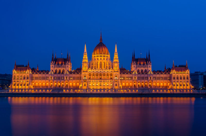 Illuminated parliament building against blue sky at night