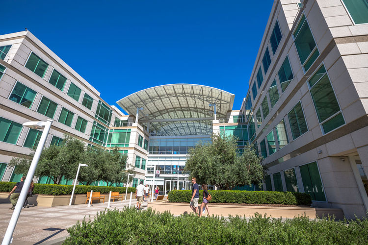 Cupertino, California, United States - August 15, 2016: the Apple world headquarters at One Infinite Loop. Apple is a multinational that produces consumer electronics, personal computers and software. people come from the popular Apple store of Apple Inc Headquarters at One Infinite Loop located in Cupertino, Silicon Valley, California. Apple California IT Mac PC United States Architecture Blue Building Building Exterior Built Structure City Clear Sky Computer Cupertino Day Electronics Industry Flag Grass Headquarter Headquarters Hq IMac27 IPhone Imac Infinite Loop Lifestyles Mobile Modern Nature Outdoors People Real People Sky Store Sunlight Tree Women