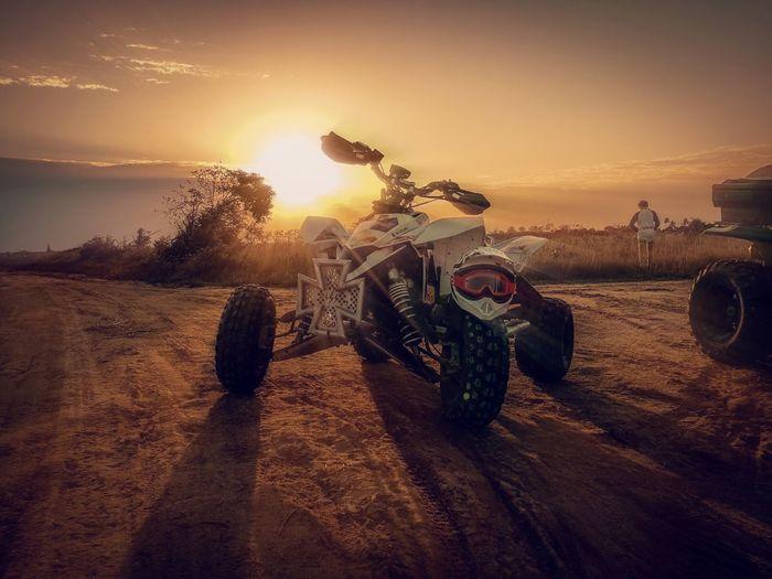 Quadbike on sand against sky during sunset