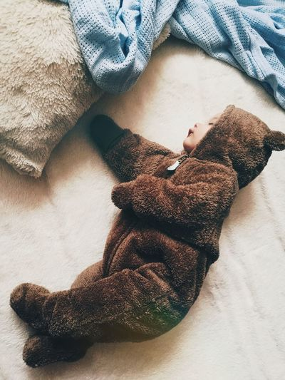High angle view of baby in bear costume sleeping on bed