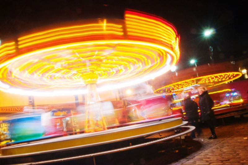 Night Illuminated Amusement Park Arts Culture And Entertainment Amusement Park Ride Blurred Motion Long Exposure Speed Carousel Leisure Activity Motion Outdoors Multi Colored Real People Men Merry-go-round Sky People