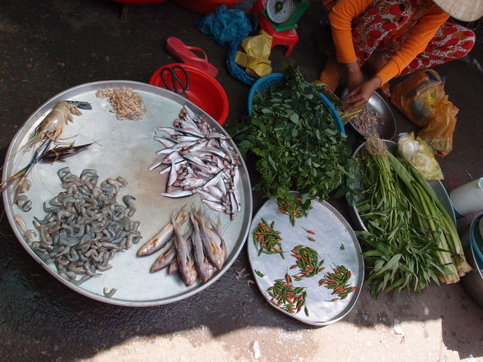 Low section of vendor selling vegetables and fish in market