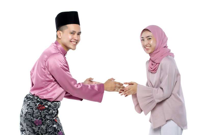 Portrait of young man with traditional clothing shaking hand his wife during hari raya over white background White Background Studio Shot Smiling Young Adult Indoors  Happiness Traditional Clothing Young Women Holding Emotion Looking At Camera Cut Out Adult Standing Three Quarter Length Young Men Side View Portrait Pink Color