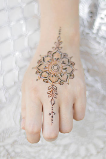 Low section of woman with tattoo on hand