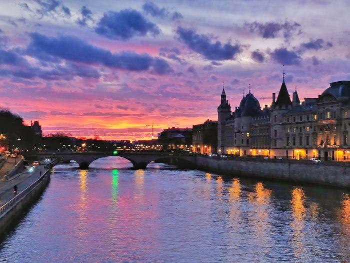 Bridge over river against buildings at sunset