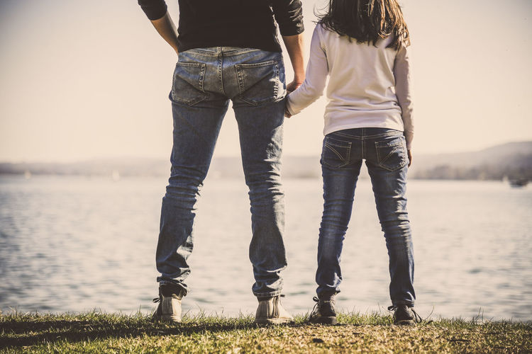 Low section of father and daughter standing by lake against sky
