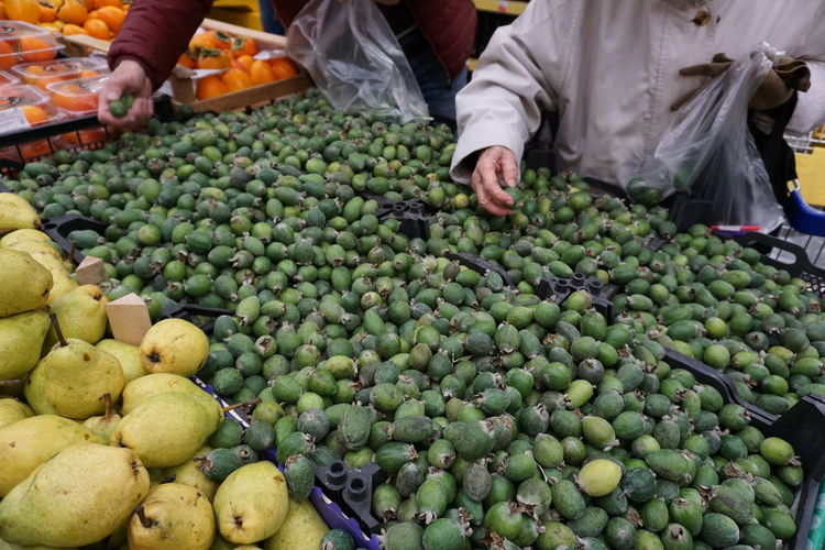 Hands of people choosing fruits in a supermarket. heap of feijoa, for sale