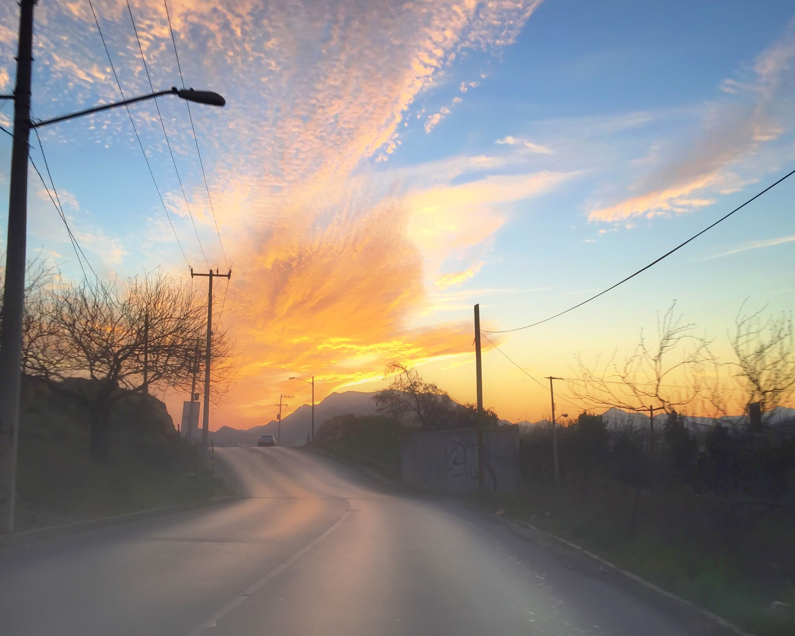 sunset, the way forward, transportation, road, sky, diminishing perspective, tree, vanishing point, cloud - sky, orange color, road marking, country road, electricity pylon, silhouette, tranquility, scenics, nature, empty road, beauty in nature, tranquil scene