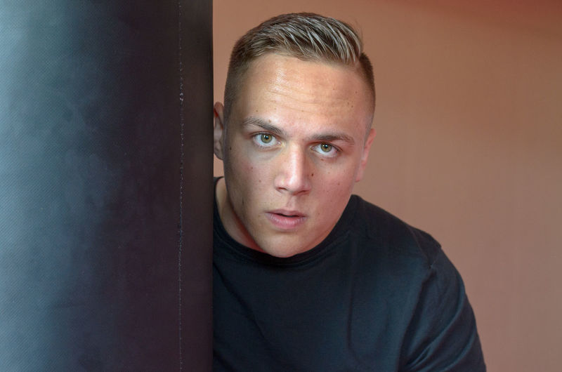 Portrait of man by punching bag against wall