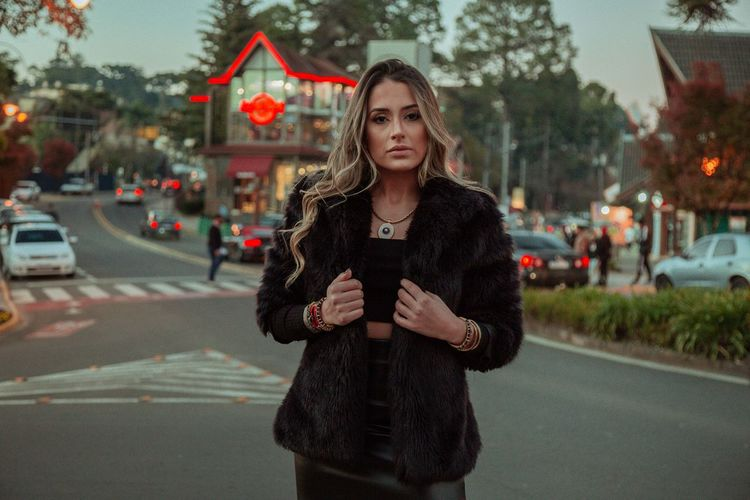 Portrait of young woman standing on road in city