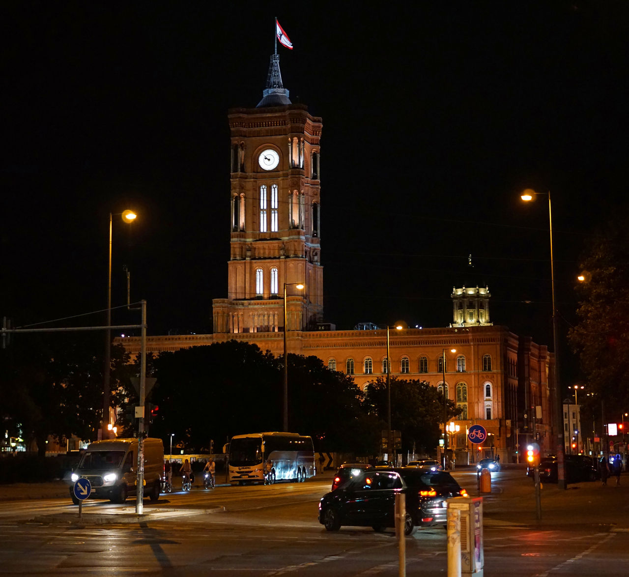night, illuminated, architecture, mode of transportation, transportation, built structure, car, city, motor vehicle, building exterior, land vehicle, street, tower, clock tower, building, street light, motion, travel, sky, road, clock