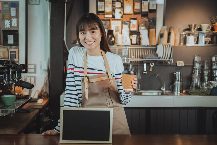 Close-Up Portrait Of Young Woman Holding Coffee Drink While Standing In Cafe