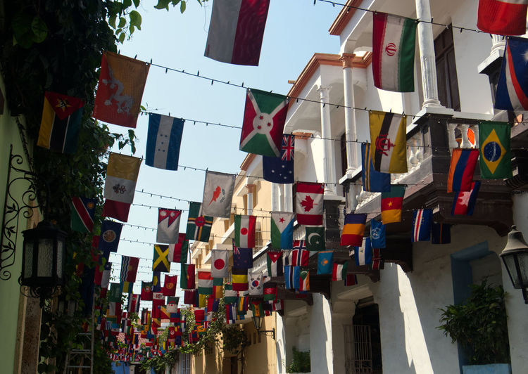 Low angle view of flags hanging amidst buildings against sky