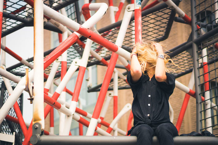 Woman sitting on metal structure against building
