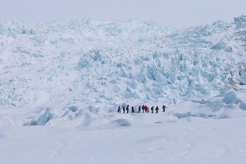 People on glacier against sky