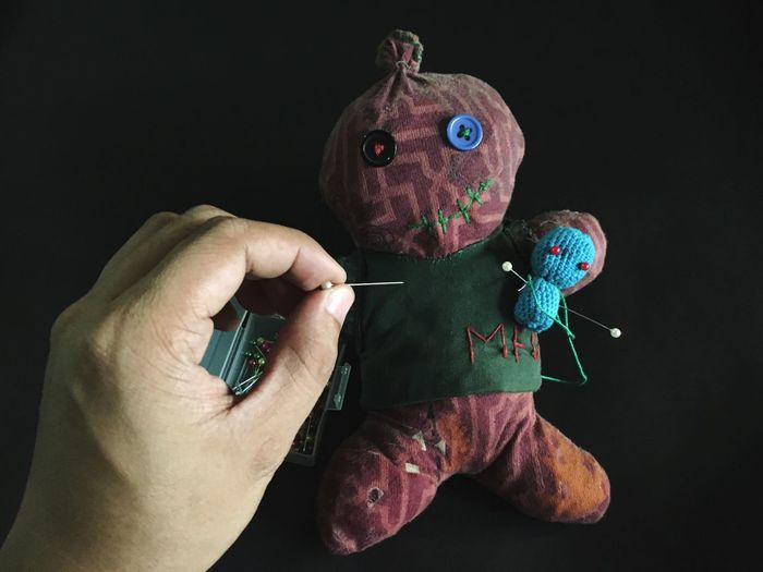 Cropped hand of man putting straight pin in voodoo doll over black background