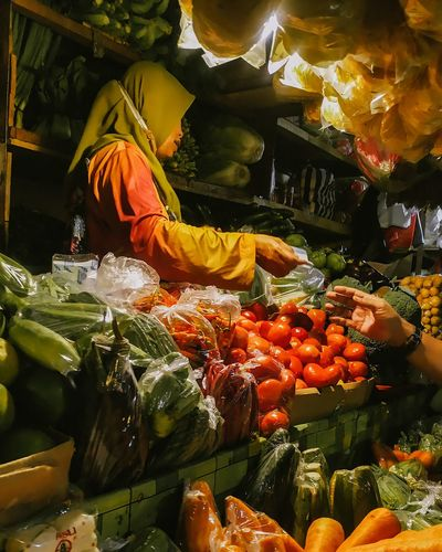 Mature woman selling various vegetables at market