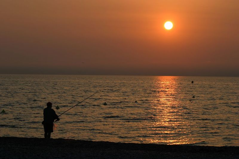 Early morning fisherman at sunrise Nice South of France Fisher Man Fisherman Cote D'Azur Antibes South of France Sillouette sea Sunrise sunset Golden Hour golden Fishing man Holiday beach Beach Sunset morning Fishing Rod